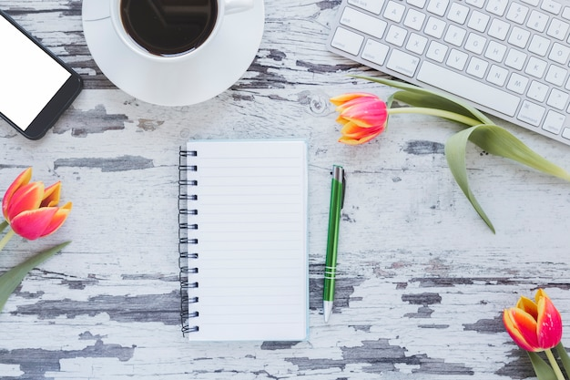 Notebook and coffee cup near keyboard and smartphone on desk with tulip flowers