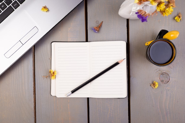Notebook, coffee and flowers for female home or office workplace,