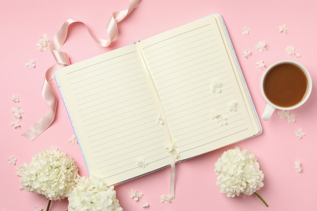 Notebook, coffee and hydrangea flowers on pink background
