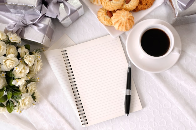 Notebook and coffee with biscuits