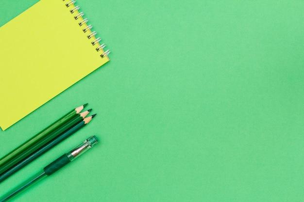 Блокнот, цветные карандаши и ручка на зеленом фоне.
