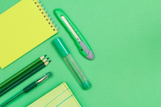 Блокнот, цветные карандаши, ручка, книга, фломастер и нож для бумаги на зеленом фоне. вид сверху с копией пространства. снова в школу концепции. школьные принадлежности