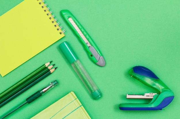 Блокнот, цветные карандаши, ручка, книга, фломастер, нож для бумаги и степлер на зеленом фоне. вид сверху. снова в школу концепции. школьные принадлежности