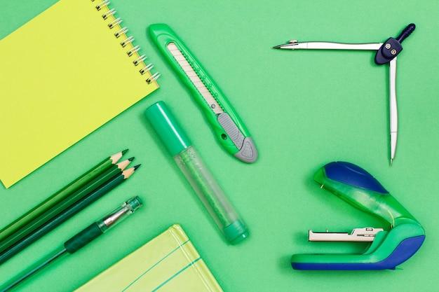 Блокнот, цветные карандаши, ручка, книга, фломастер, нож для бумаги, компас и степлер на зеленом фоне. вид сверху. снова в школу концепции. школьные принадлежности