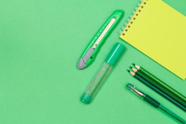 Блокнот, цветные карандаши, ручка, фломастер и нож для бумаги на зеленом фоне.