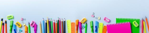 Блокнот, цветные карандаши, линейка, ручка, ластик, точилка и многое другое. канцелярские товары школы и офиса на синем