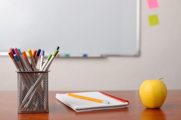 노트북, 색연필 및 교실 테이블에 사과