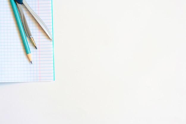 Блокнот, компас и карандаш на белом фоне, копией пространства