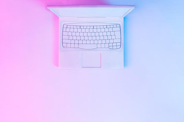 노트북 컴퓨터 또는 노트북은 흰색으로 칠해진 생생한 굵은 그라데이션 보라색 및 파란색 홀로그램 색상 조명. 컨셉 아트. 최소한의 사무실 초현실주의.