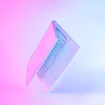 흰색으로 칠해진 노트북 컴퓨터 또는 노트북과 생생한 대담한 그라데이션 퍼플 및 블루 홀로그램 컬러 조명