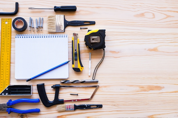 Notebook and construction tools, on a wooden table top view with copyspace