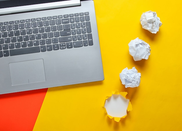 Notebook, crumpled paper balls, on a yellow table with a torn hole