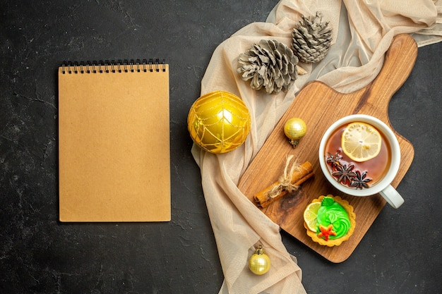 Notebook and a cup of black tea with lemon and cinnamon limes new year decoration accessories on wooden cutting board