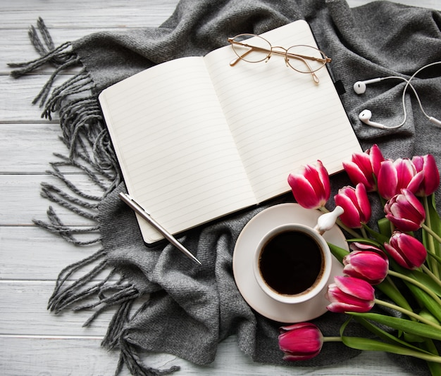 Notebook, cup of coffee  and pink tulips