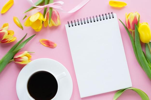 Ноутбук, чашка кофе, красочные тюльпаны на розовом фоне