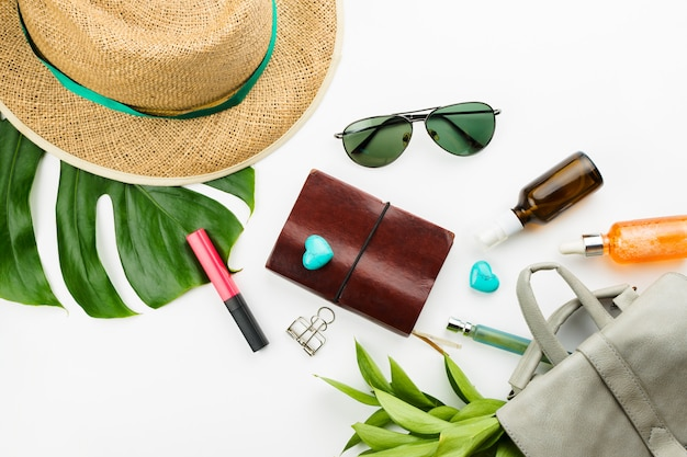Notebook, dark glasses, grey backpack, cosmetics, straw hat and monstera leaves