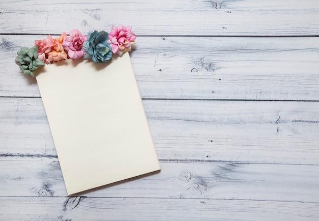 木製の背景に色とりどりの花で飾られたノートブック。 Premium写真