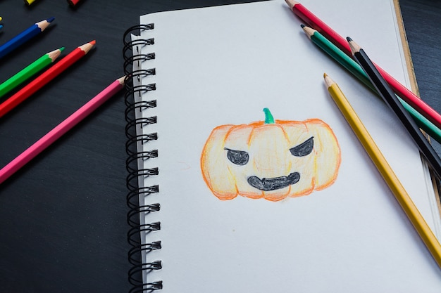 Notebook on the desk, drawing  pumpkin on the notebook