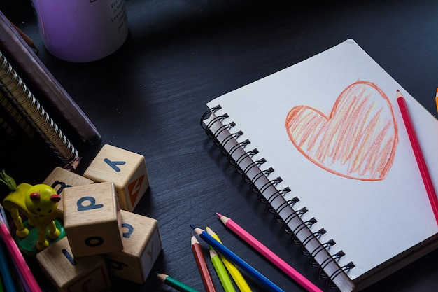 Notebook on the desk, heart drawing on the notebook
