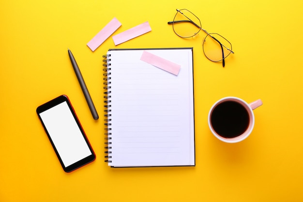 Notebook, eye glasses, cup of cofee, pen , mobile phone, stickers on yellow background. flat lay, copy space.
