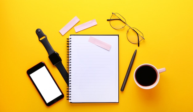 Notebook, eye glasses, cup of cofee, pen , mobile phone, stickers on yellow background.