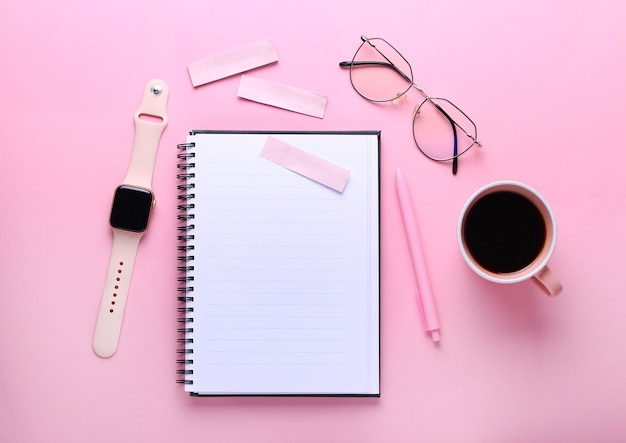 Notebook, eye glasses, cup of cofee, pen ,smart watch on pink background.