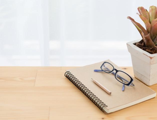 Блокнот, очки, цветочный горшок и коричневый карандаш на деревянном столе
