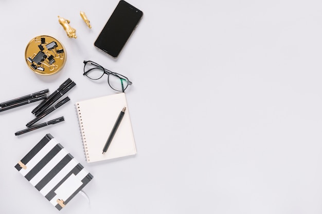 Notebook; felt-tip pen; eyeglasses; stationery and cellphone on white background