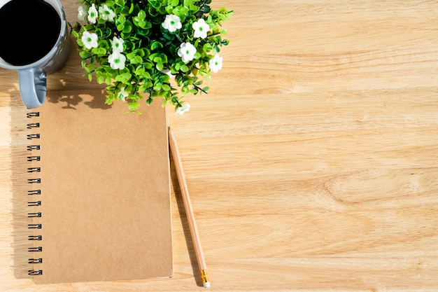 Notebook,flower pot tree,a pencil and coffee cup on wooden background,top view with  office table.