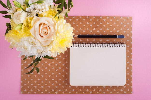 Notebook, flowers and lit candle background