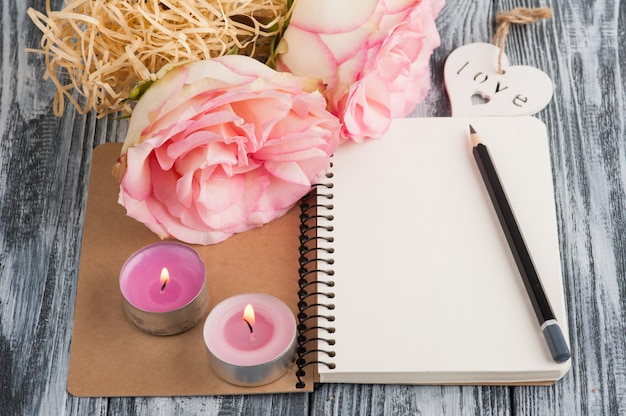Notebook, flowers and lit candles