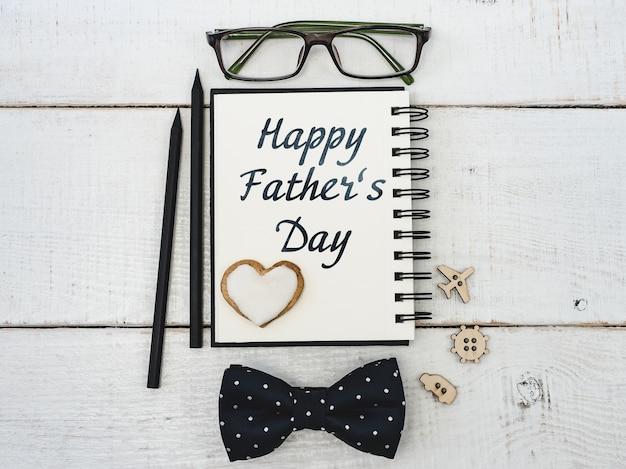 Блокнот для поздравления отца, очки, карандаш, ручка на красивом, белом столе. вид сверху крупным планом. подготовка к празднику