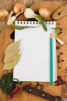 Блокнот для приготовления рецептов и специй на деревянном столе