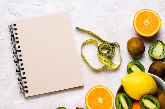 Блокнот для записей, рулетка и органические фрукты на светлом фоне камня