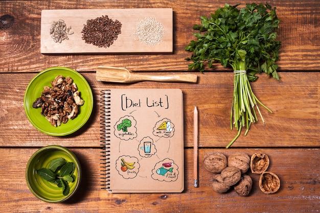 Записная книжка для рецептов, карандаш, грецкие орехи, петрушка и семена на деревянном столе. концепция диеты