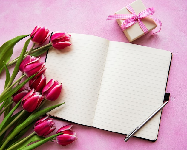 Notebook, gift box and pink tulips