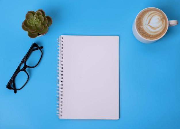 Ноутбук, очки, чашка кофе и растения на синем фоне
