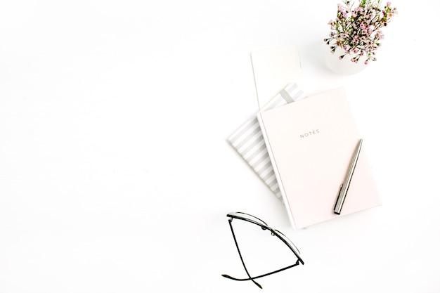 白い背景にノート、メガネ、ペン、ワイルドフラワー。フラットレイ、トップビュー