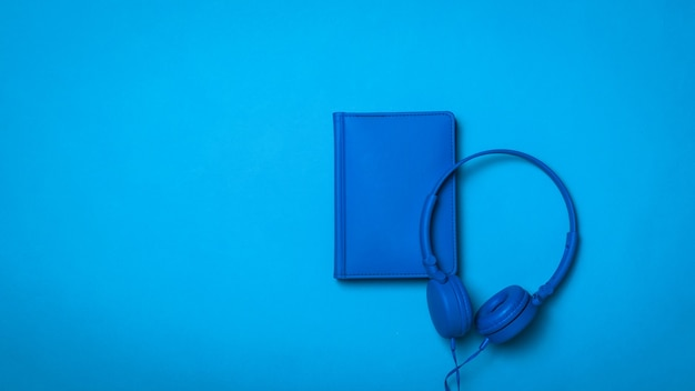 Notebook and headphones with a wire in a blue surface. monochrome image of office accessories.