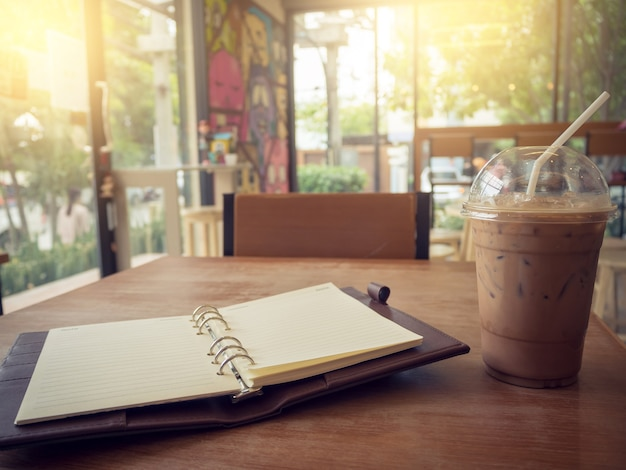 Notebook and ice coffee on wooden background