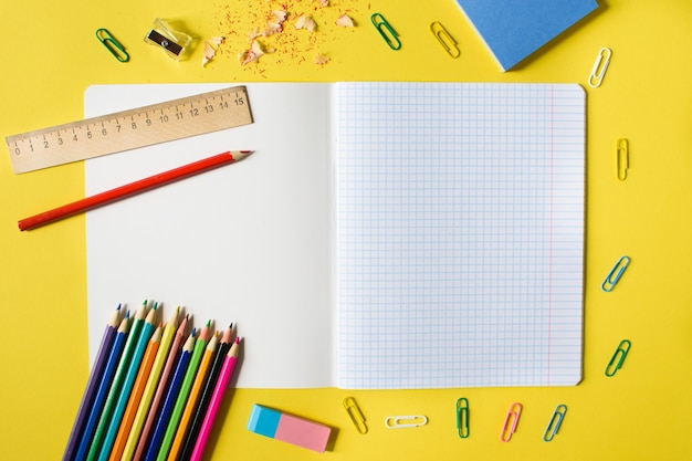 黄色の背景に鉛筆、消しゴム、定規、ペーパークリップ、その他の事務用品が入った檻の中のノート。学校に戻るコンセプト。テキストの場所。