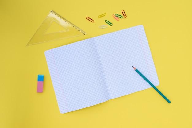 黄色の背景に鉛筆、消しゴム、定規、ペーパークリップが付いている檻の中のノート。学校に戻るコンセプト。テキストの場所。