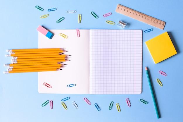 青い背景に鉛筆、消しゴム、定規、ペーパークリップ、その他の事務用品が入った檻の中のノート。学校に戻るコンセプト。テキストの場所。