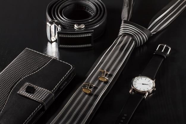 가죽 커버의 노트북, 넥타이, 커프스 단추, 금속 버클이 있는 가죽 벨트, 검정색 배경에 가죽 스트랩이 있는 시계
