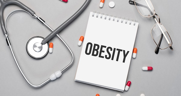 In the notebook is the text obesity, next to a stethoscope, pills and glasses.