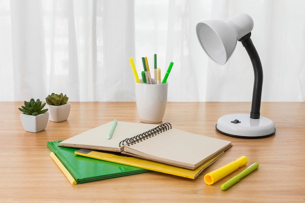 Notebook and lamp on desk high angle