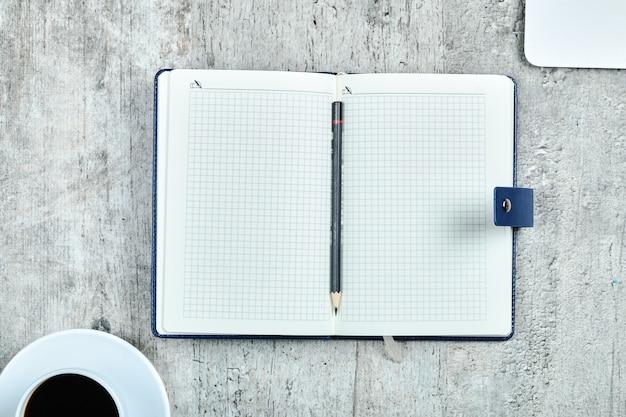 ノートブック、ラップトップ、木製の机の上のお茶。