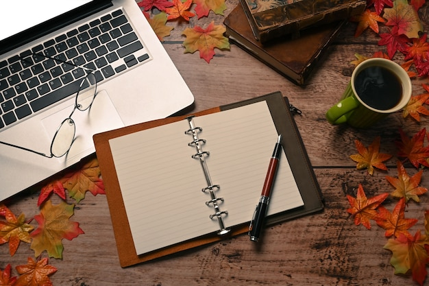 Notebook, laptop computer, coffee cup and autumn maple leaves on wooden background.