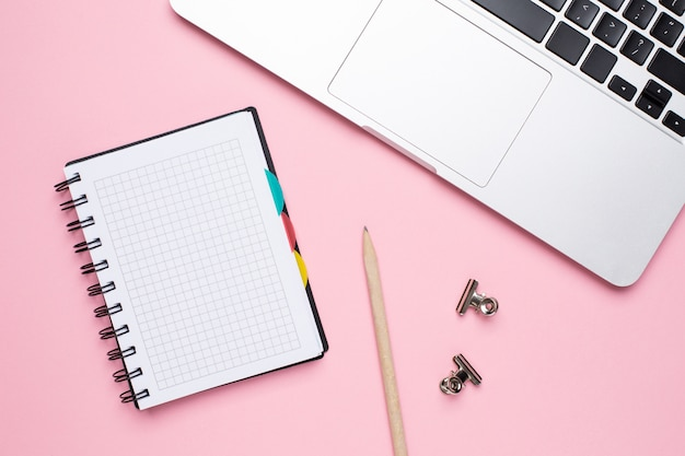 Notebook and laptop on a pink background