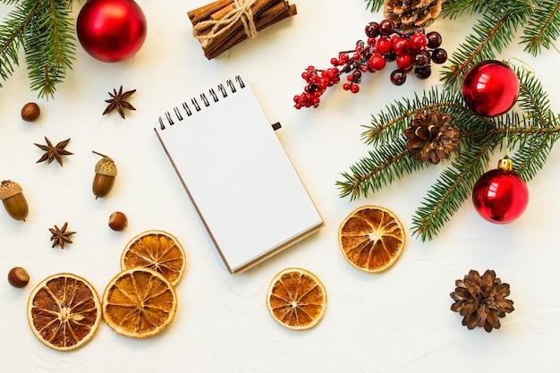 텍스트를 기록하는 노트북 레이아웃. 가문비나무와 열매의 오렌지 조각, 견과류, 공, 가지의 평평한 레이아웃 위에서 볼 수 있습니다.